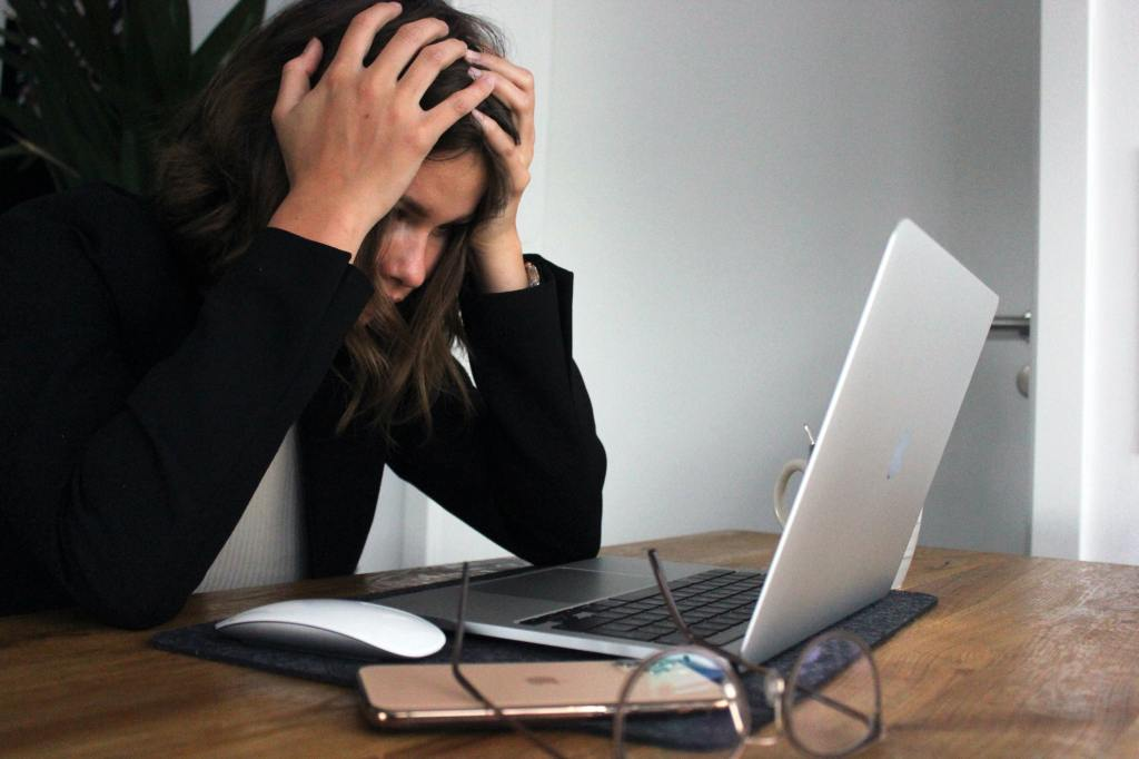 Woman looking at a computer with her head in her hands